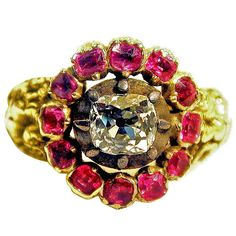 Antique Diamond Ruby Gold Ring. Fantastic Georgian diamond ring in an 18K chased gold setting surrounded by twelve cushion cut rubies. The diamond is cushion cut and weighs approximately .45 carats. Its clarity is VS and color is H-J, c 1830