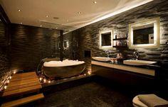 De combinatie van het sfeerlicht en de materialen in deze badkamer vinden wij fantastisch.
