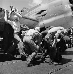 Flight deck crew on USS Lexington CV-16 move an aircraft with a flat tire Nov. 1943