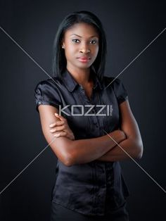 smart young businesswoman with arms folded. - Portrait of a smart young businesswoman with arms folded over black background, Model: Vanessa Mitchelle