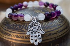 What you see is what you get - this is the only one of this bracelet I will make! Get it before its gone! - Purple striped agate round beads - Quartz round beads - Silver tone star shape spacer beads - Silver tone Hamsa Hand charm - 7 Inches un-stretched (approximately). This bracelet best fits people with a small/medium frame. - Ships from Canada.  Plagued by evil spirits? No longer with this bracelet! The Hamsa Hand charm will provide you with protection. Not only will you be safe, but…