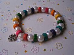 """Pulsera con perlas blancas y piezas de madera de colores, lleva el """"charm"""" de corazón Made with love"""