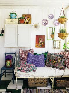 An antique iron bed provides the perfect spot for a postprandial nap. The cushions are made from scraps of vintage floral fabric. For similar fabric, try Sarah MooreHome (sarahmoorehome.co.uk). Vintage Flower Paintings (vintageflowerpaintings.com) specialises in vintage floral artwork
