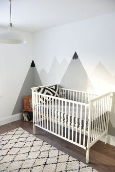 Looking for an amazing kids room or nursery decor idea? DIY this painted mountain range mural - easy and budget friendly! Perfect for a graphic, black and white, camping, adventure style room. Has a scandinavian modern vibe when done in the gray and white. Click over on to the blog for the full how-to tutorial. #kidsroom #nursery #interiordecorating #interiodesign