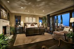 Mediterranean Master Bedroom with Cement fireplace, interior wallpaper, Crown molding, High ceiling, Hardwood floors, Carpet