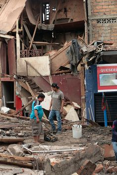 Men stand amidst rubble after a 7.8 magnitude quake in Portoviejo Ecuador on April 17 2016 At least 77 people were killed when a powerful earthquake...