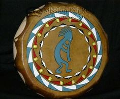Native American drum with beautiful art hand painted according to Lakota tradition featuring the black bonnet warrior pattern surrounding Kokopelli, the ancient flute player that provided abundance, rain and fertility.