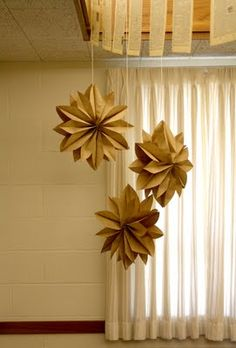 folded brown paper stars. we did these last year with 3D and normal paper snowflakes - another option - using various colored papers. spray painting the edges and adding glitter for a little sparkle.