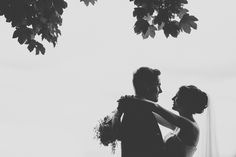 Silhouette of a bride and groom, on their wedding day, under a tree, in love, by the seaside in Scarborough, Yorkshire.