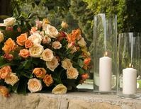 Lush, natural-looking arrangements of soft orange roses are surrounded by pillar candles in tall vases.