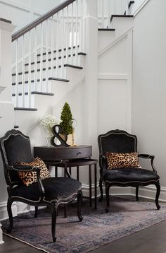 Chic foyer features a pair of black velvet French chairs accented with silver nailhead trim lined with leopard pillows flanking  wood nesting tables.