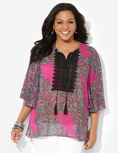 A visual stunner, this silky, semi-sheer blouse enchants with its ornate floral print on a bright backdrop. A crochet applique with dangling tassel ties adds delicate detail to the neckline. Three-quarter sleeves. Catherines tops are perfectly proportioned for the plus size woman. catherines.com
