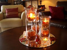 Fall Centerpiece. Glittered pumpkins and voltives on falll colored glass beads inside cylinder clear vase. The source has lots of pretty centerpieces