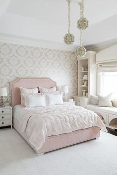Three staggered flower chandeliers illuminate a gray damask accent wall lined with a blush pink velvet bed dressed in pink shams and pink ruched duvet flanked by white french nightstands and pink glass lamps.