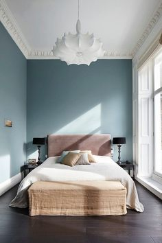 Bedroom with high-ceilings, classic crown molding, bay blue walls, a large white chandelier, and a blush headboard