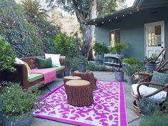 Bohemian Outdoor Space  A bold, colorful area rug can transform a boring outdoor space into a lively area for entertaining. Designer Emily Henderson created this bohemian outdoor room with a patterned area rug, stumps-turned-cocktail-tables and basic string lights.