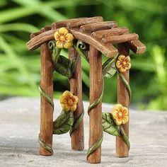 Fairytale Garden Arbor www.teeliesfairygarden.com This fairy tale arbor features adorable yellow blooms wrapped on a wooden designed polystone. #fairyarbor