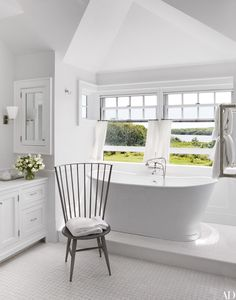 A perfectly serene all-white bathroom has a spectacular view as well.