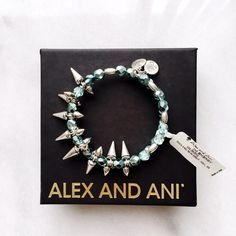"""⚬Alex and Ani⚬Teal Rock and Raw Bangle Super cute piece that will quickly become your jewelry box staple!                                                     Details: Silver-tone wire bracelet wrapped with assorted teal beads and spike studs - Expandable - Approx. 2.5"""" resting diameter - Approx. 0.75"""" L x 0.75"""" W pendant - Approx. 0.5"""" mini charms  Materials: Rafaelian silver-tone recycled metal, glass beads. Brand new with tags and dust bag. *Box not included. Would make a great holiday…"""