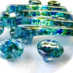 """Torch Lake is a signature blend of hand cut glass frit in  transparent blues and greens accented with bits of transparent dichroic sparkle.  Available in 1.25"""" round, 1.5"""" square, 2"""" round, handle on 3"""" center or as tiles.  Knobs, handles and pulls make beautiful cabinet hardware for kitchens and bathrooms."""