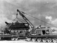 M88A1 Recovery Vehicle Vietnam 1971 Boom extended loading an Armored Personnel Carrier on an flatbed trailer.