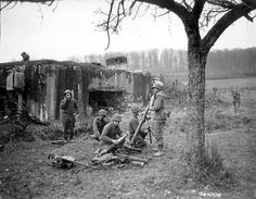 American soldiers are preparing to open fire with an 81-mm M1 mortar, from next to an abandoned bunker in France.