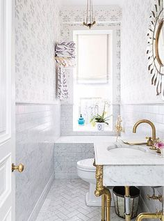 CeCe renovated the apartment's diminutive bathroom, adding a petite (and perfectly kid-size) tub. Custom-colored wallpaper matches the tones in the marble; the monochromatic look helps the space feel more expansive.