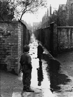 © Shirley Baker  Two Boys Playing in a Large Puddle - Manchester, 1966