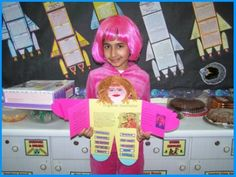 """Character Body Book Report Projects:  This student is holding the Violet Beauregarde (from """"Charlie and the Chocolate Factory"""" by Roald Dahl) project that she designed.  She's written a description inside the shirt area and glued adjectives that describe Violet Beauregarde on the outside of the arms and legs.  Directions and templates for assembling these fun """"character body book report projects"""" are available on Unique Teaching Resources."""