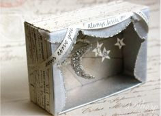 """silvery: mini diorama with glittered moon and stars embellished with printed ribbon with saying """" never above you always beside you"""" made by D Sharp How about dioramas / shadowboxes of stories, fairy tales, nursery rhymes Shadow Box Kunst, Shadow Box Art, Matchbox Crafts, Matchbox Art, Craft Projects, Crafts For Kids, Arts And Crafts, Paper Crafts, Altered Tins"""