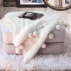 Plaid in Wollweiß aus kuscheligem Strick mit Fake-Fur-Kanten und Bommeln. 46% Acryl, 36% Wolle, 10% Baumwolle, 8% Nylon. Ca. 170 x 130 cm.    Bestellnummer: 5088178    € 119,00