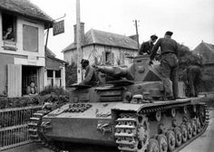A German Panzer III, Normandy, France. June, 1944. (Actually it's a Panzer IV.) Panzer III's have three guide wheels on top, while a Panzer IV has four.