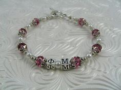 Phi Mu bracelet features Sterling Silver Greek letters and pink Swarowski crystals and white pearl beads.  Standard length is approximately 7, which fits a medium wrist. If you need the item sized differently, please contact me and I can adjust the length for you!  Bracelet features sterling silver 4.5mm Greek lettering and beads in sorority colors in 6mm Swarowski crystals and 4mm glass pearl beads. Bead caps and little beads are base metal, as is the easy-to-use toggle clasp.  Great gift…