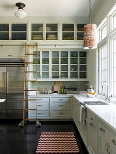 I really like that this kitchen is very cute and extremely functional it has lots of storage which is always important and they found a creative way to include access to those high storage cupboards reusing the old library ladder in a new innovative way. LOVE