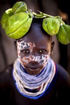 Een jong Karo meisje met een bijzonder hoofddeksel. Een zeer giftige plant, maar fotogeniek, dus zet ze het maar op haar hoofd. De Karo leven net langs de Omo rivier in het zuiden van Ethiopië en zijn met uitsterven bedreigd. In hun gebied wordt een suikerrietplantage opgericht en vele Karo zullen daar moeten gaan werken om te kunnen overleven; aangezien ze niet genoeg land en water meer hebben om hun vee te laten grazen of om gewassen te telen. Door communitylid StevenG - NG ReisCommunity ©