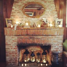 A beautiful, rustic brick fireplace with glowing lanterns, candles, books, lace, flowers and photographs.
