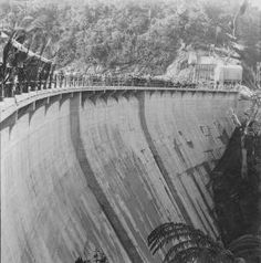 Official opening of the Nihotupu Dam, completed 1923. A canvas canopy was erected (left), decorated with palm leaves and under-neath were trestle tables laden with drinks for the guests. http://www.aucklandmuseum.com | Auckland Museum