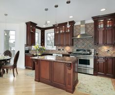 Luxury kitchen with cherry cabinets and red stone tile backsplash with black granite counters.