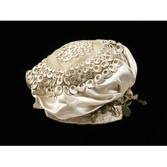 1818-1823. Early 19th-century etiquette required a lady's head to be covered at all times, even with evening dress. A cap such as this one, gathered and full to suggest the shape of a turban, was popular for evening wear about 1820.