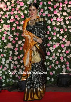 Rekha attended Kapil Sharma and Ginni Chatrath's wedding reception wearing a black checkered Kanjeevaram silk saree paired with orange blouse. Traditional gold jewelry, gold potli bag and flowers in hair rounded out her look! Indian Wedding Gowns, Indian Bridal Sarees, Wedding Silk Saree, Kanjivaram Sarees Silk, Kanchipuram Saree, Fancy Sarees, Party Wear Sarees, Dress Indian Style, Indian Dresses