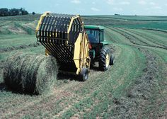 Here's an Iowa farmer riding his John Deere tractor making big round bales of hay.