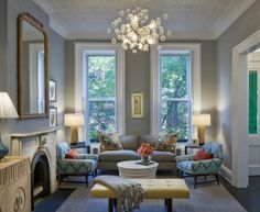 gorgeous blue & gray chic living room design with gray blue walls paint color, gray modern sofa, Oly Studio Pipa cocktail table, limed oak French key 4 door cabinet with nickel plated brass rings, yellow leather modern tufted bench, white & turquoise blue chairs, limestone fireplace, chiang mai pillows, faux bamboo mirror, gray rug and modern bubbles glass chandelier.