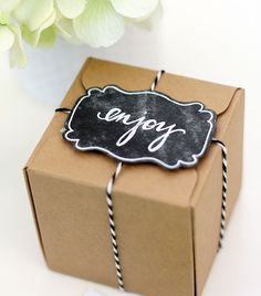 Turn a regular piece of black construction paper into a cute chalkboard gift tag that will make your present stand out from the crowd.