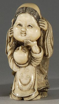 IVORY NETSUKE ~ 19th Century ~ By Meizan.  Depicting Hotei with an okame mask entertaining a small child. Signed.