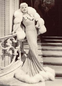 Heretic, Rebel, a Thing to Flout: Mae West Introduces Americans to—Gasp!—Sex.  She was a tiny lady, barely five foot tall.  It was more than her trademark Gay '90's plumed hats that made her seem much bigger.  It was a bold, brassy, and irreverent persona that challenged everything puritanical America valued in submissive, virtuous, sexless, and dependent womanhood.