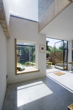 A Projecting Frameless Glass Box Oriel Window Seat with Timber reveals, Frameless Rooflight and French Doors
