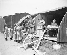Clothing is being issued by the Women's Army Auxiliary Corps (WAAC) from a Nissen hut damaged by an air raid at Abbeville, 22 May 1918. Photographer: Lieutenant John Warwick Brooke. IWM Q 7885.