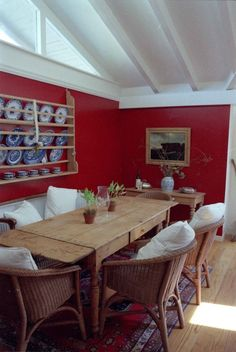 Red room with whited ceiling. Plate rack on wall with blue and white plates. Nice pine table.