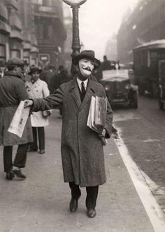 Newspaper Seller with a Mask in Paris, 1929.  Photographer: Het Leven.