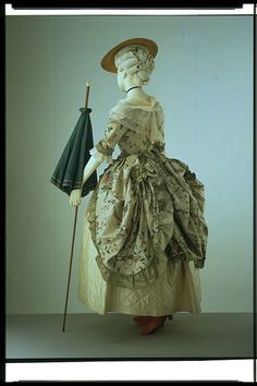 Parasol and hand-painted silk polonaise gown from the late 1770s: This long walking cane with an ivory hook features a green silk parasol midway down its length. The parasol is carried with the cover pointing upwards, which was typical for early parasols, as there was no latch to hold the cover closed when it was inverted.